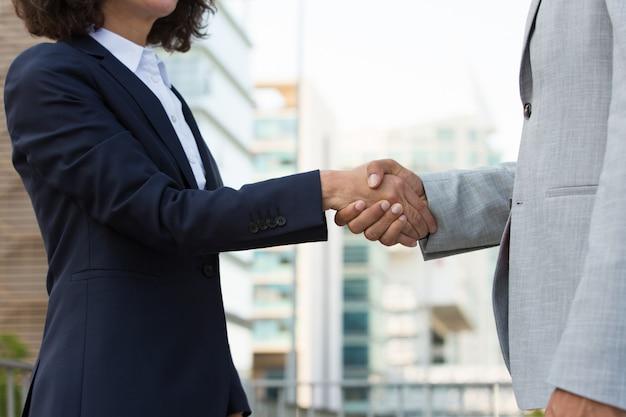 Mannelijke en vrouwelijke collega's die elkaar in stad begroeten