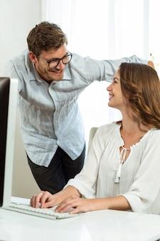 Mannelijke en vrouwelijke collega's die terwijl het gebruiken van computer bij bureau glimlachen
