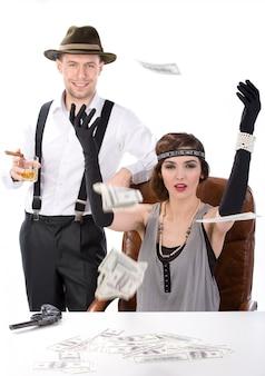 Mannelijke en vrouwelijke gangsters zitten aan een tafel tellend geld.