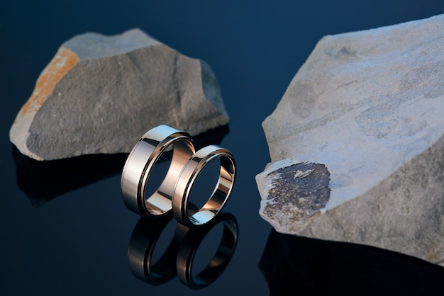 Mannelijke en vrouwelijke gouden trouwringen onder stenen