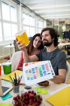 Mannelijke en vrouwelijke grafisch ontwerpers die plastic container en kleurenkaart