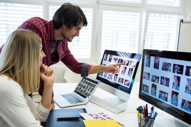 Mannelijke en vrouwelijke grafisch ontwerpers interactie via computer
