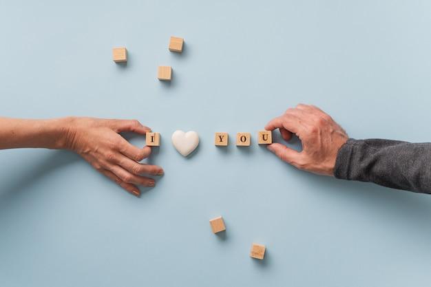 Mannelijke en vrouwelijke hand die een i love you-bord maken, gespeld op houten blokken met hartvormig marmer in het midden.