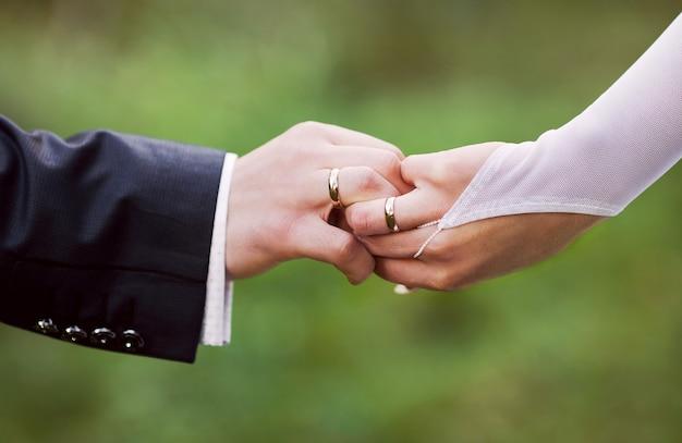 Mannelijke en vrouwelijke hand met een trouwring