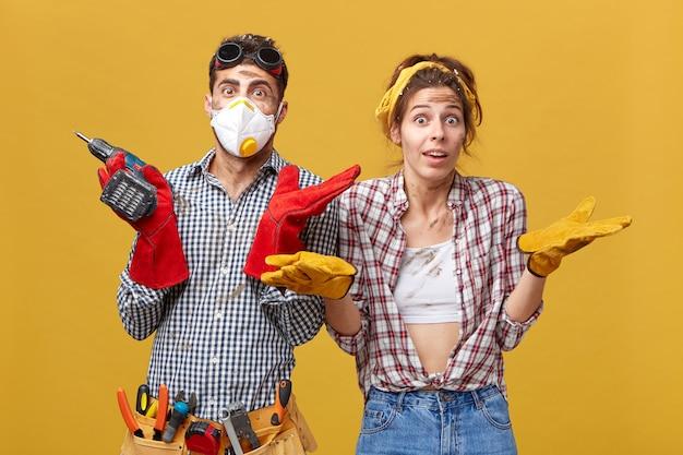 Mannelijke en vrouwelijke handarbeiders halen hun schouders op met twijfelachtige uitdrukkingen, niet wetend waarmee ze aan hun werk moeten beginnen. jonge man met boormachine met enkele twijfels en onzekerheid