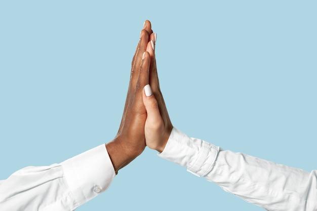 Mannelijke en vrouwelijke handen aanraken geïsoleerd op blauw.