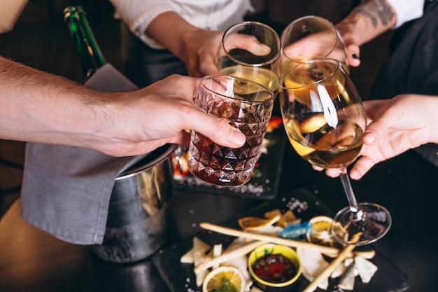 Mannelijke en vrouwelijke handen close-up met cocktails