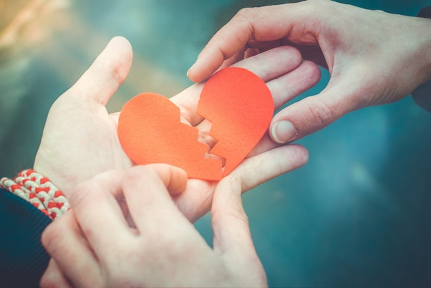 Mannelijke en vrouwelijke handen die een gebroken hart herstellen. scheidingsconcept. hou van concept