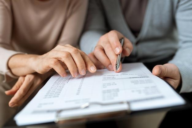 Mannelijke en vrouwelijke handen die op document wijzen tijdens het bespreken van voorwaarden en punten van contract