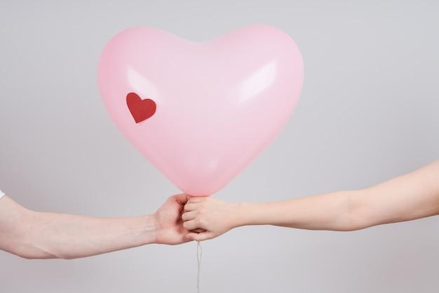 Mannelijke en vrouwelijke handen houden een hartvormige ballon tegenover elkaar. fijne valentijnsdag.