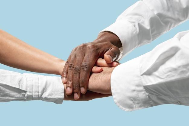 Mannelijke en vrouwelijke handen houden geïsoleerd op blauw.