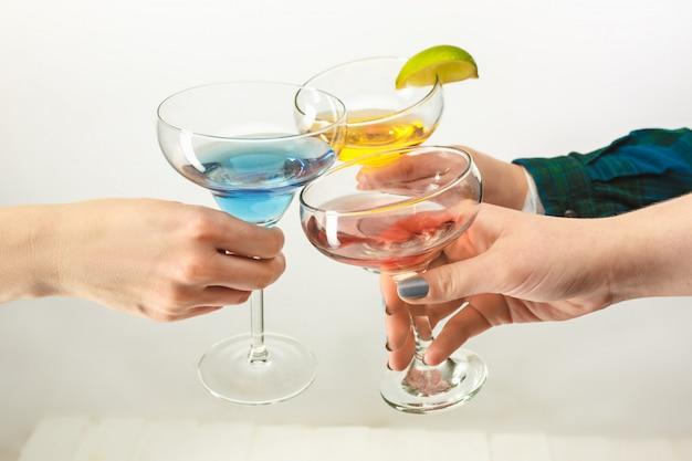 Mannelijke en vrouwelijke handen met exotische cocktails