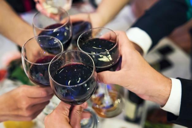 Mannelijke en vrouwelijke handen met gevulde glazen rode wijn boven het tafelblad van het restaurant. het drinken van toast en rammelende bekers op een formeel etentje. wijn drinken bij een banket. in volle gang van het feest.