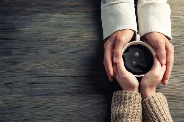 Mannelijke en vrouwelijke handen met koffie op houten