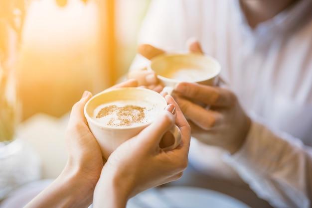 Mannelijke en vrouwelijke holding kopjes warme drank