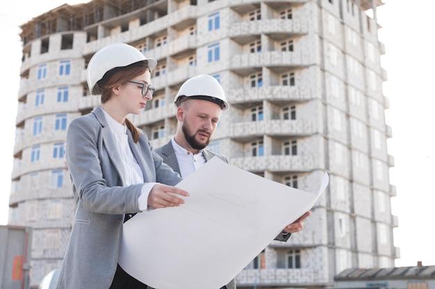 Mannelijke en vrouwelijke ingenieur die blauwdruk terwijl het werken op bouwplaats