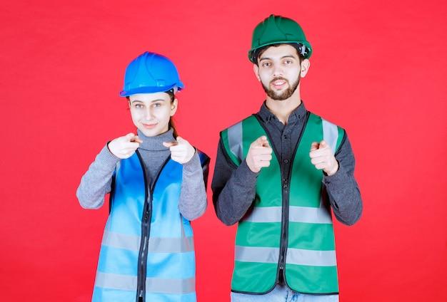 Mannelijke en vrouwelijke ingenieurs die een helm en uitrusting dragen en de persoon voor zich opmerken.