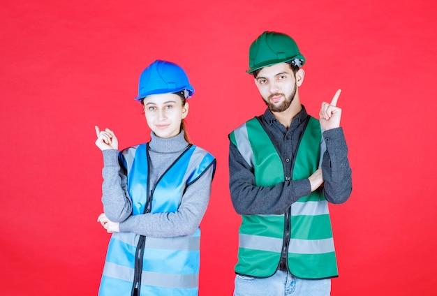 Mannelijke en vrouwelijke ingenieurs die helm en uitrusting dragen die verschijnen.