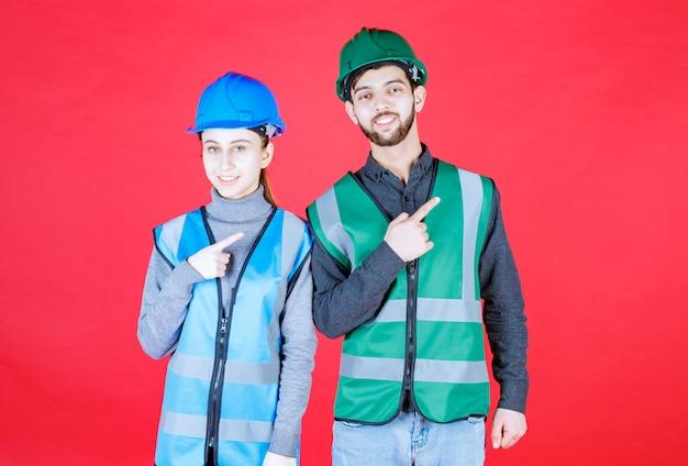 Mannelijke en vrouwelijke ingenieurs die helm en vistuig dragen die naar de rechterkant wijzen.