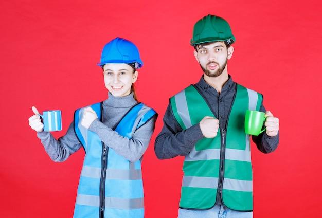 Mannelijke en vrouwelijke ingenieurs die met helm blauwe en groene mokken houden en tevredenheidsteken tonen.