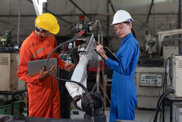 Mannelijke en vrouwelijke ingenieurs inspectiecontrole robotarm lasmachine met een laptop in de fabriek