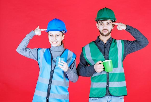 Mannelijke en vrouwelijke ingenieurs met helm die blauwe en groene mokken vasthouden en nadenken over nieuwe ideeën.