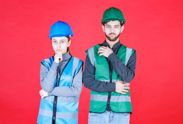 Mannelijke en vrouwelijke ingenieurs met helm en uitrusting zien er verward en attent uit.