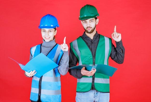 Mannelijke en vrouwelijke ingenieurs met helmen die blauwe mappen vasthouden, deze lezen en mededelingen doen.