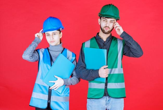 Mannelijke en vrouwelijke ingenieurs met helmen die blauwe mappen vasthouden en zien er verward en attent uit.