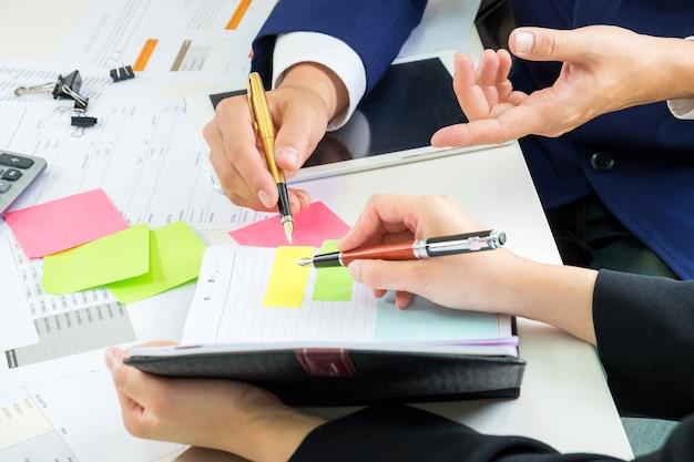 Mannelijke en vrouwelijke kantoormedewerkers werken en maken aantekeningen.