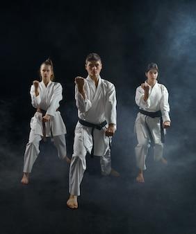 Mannelijke en vrouwelijke karatestrijders in witte kimono, groepstraining. karatekas over training, vechtsporten, vechtwedstrijden