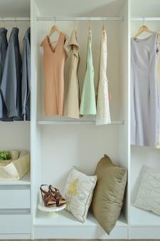 Mannelijke en vrouwelijke kleding die op hangers in garderobe hangen