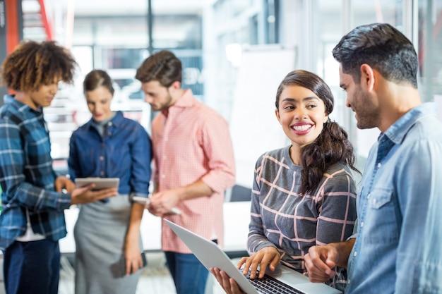 Mannelijke en vrouwelijke leidinggevenden met discussie over laptop