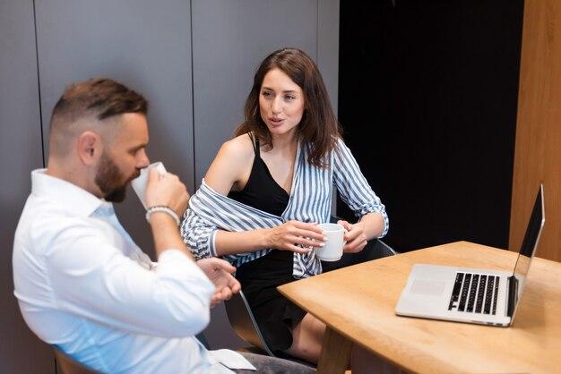 Mannelijke en vrouwelijke managers zitten aan tafel met een kopje koffie en bespreken werkproblemen