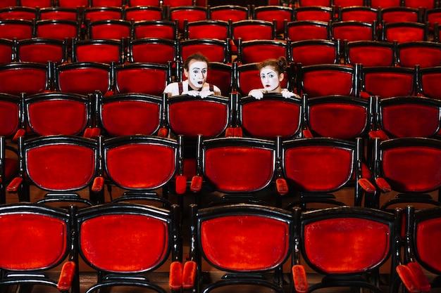 Mannelijke en vrouwelijke mimespeler verbergen zich achter de rij fauteuils