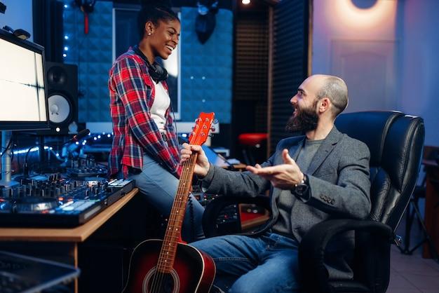 Mannelijke en vrouwelijke muzikanten in geluidsopnamestudio. artiesten op record, professionele muziekmixing