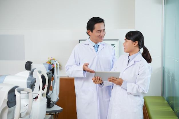 Mannelijke en vrouwelijke oftalmologen die iets op tablet in de ruimte van het oogonderzoek bespreken