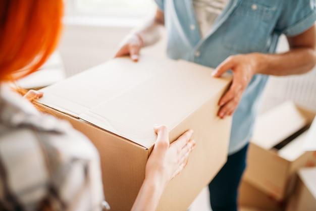 Mannelijke en vrouwelijke persoon handen houdt kartonnen doos, housewarming. verhuizen naar een nieuw huis