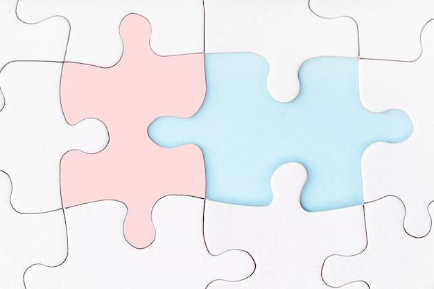 Mannelijke en vrouwelijke puzzelstukjes passen bij elkaar. ontbrekende stukje puzzel op blauwe achtergrond.