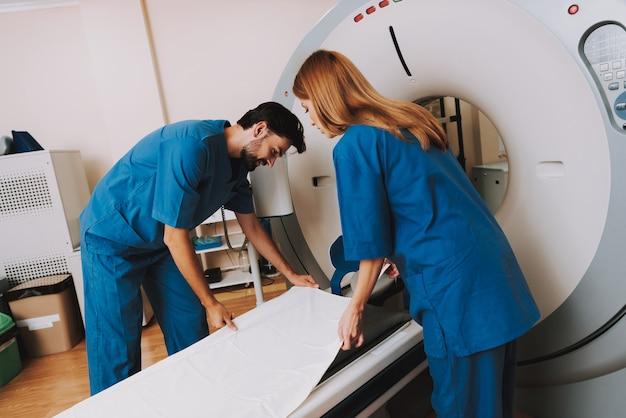 Mannelijke en vrouwelijke radiologie-artsen bij ct machine.