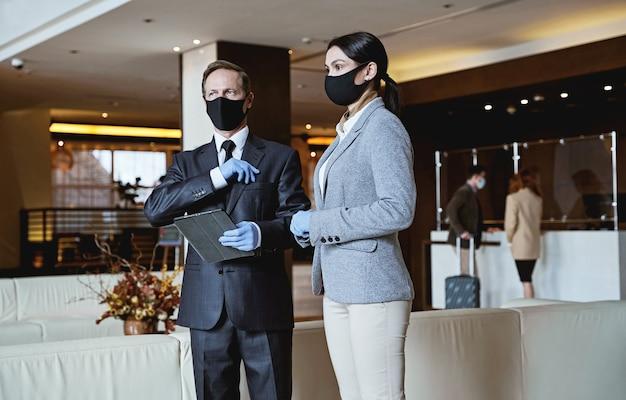 Mannelijke en vrouwelijke receptionisten die veiligheidsmaatregelen volgen en maskers dragen terwijl ze in de lobby van het hotel staan