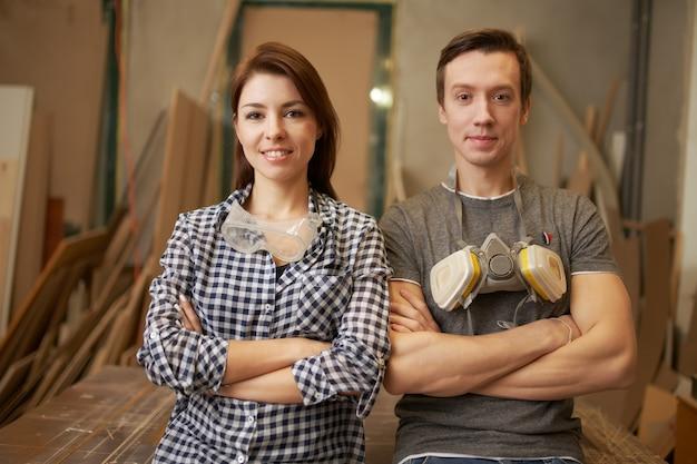 Mannelijke en vrouwelijke schrijnwerkers met gekruiste armen in werkplaats