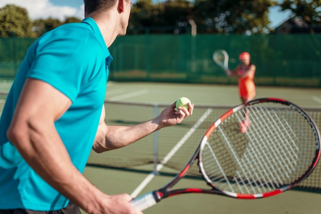 Mannelijke en vrouwelijke spelers met rackets op de tennisbaan buiten.