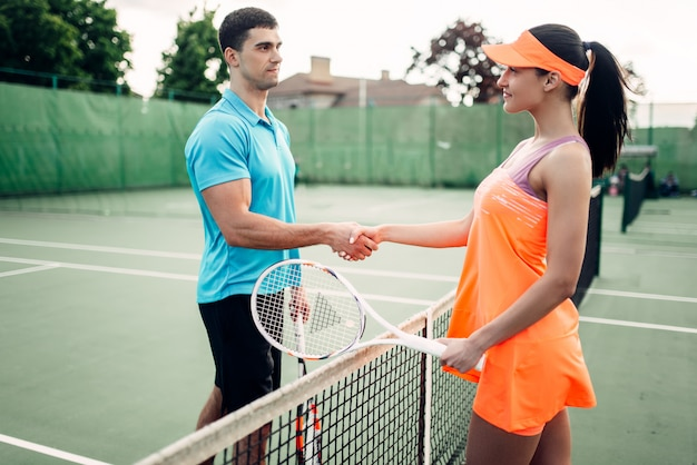 Mannelijke en vrouwelijke spelers op de tennisbaan buiten.