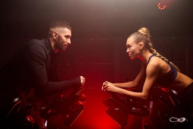 Mannelijke en vrouwelijke sportmensen houden competitie op de fiets in de sportschool geïsoleerd op rode neon verlichte rokerige ruimte, oppsite van elkaar