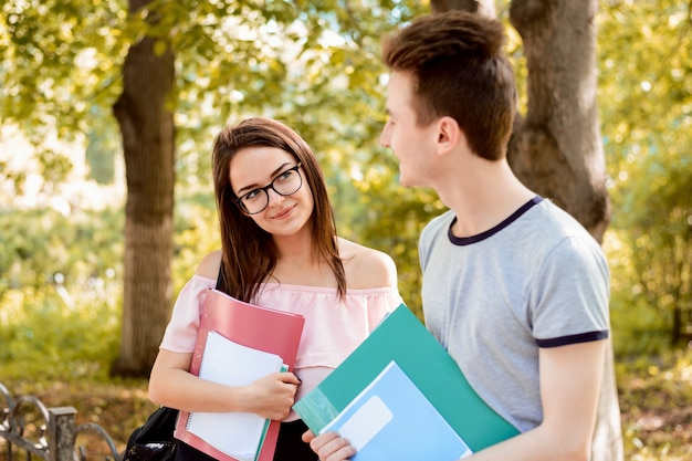 Mannelijke en vrouwelijke studenten die gesprek in openlucht in het park na klassen hebben