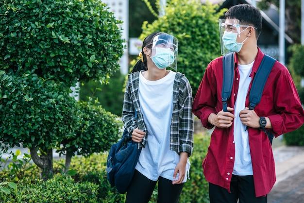 Mannelijke en vrouwelijke studenten dragen een chill gezicht en maskers. loop over het voetpad