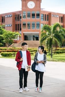 Mannelijke en vrouwelijke studenten dragen een gezicht chill en staan voor de universiteit.