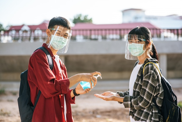 Mannelijke en vrouwelijke studenten dragen maskers en knijpen in de gel om hun handen te wassen.