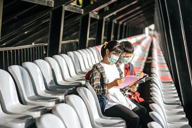 Mannelijke en vrouwelijke studenten dragen maskers en zitten en lezen op de veldstoel